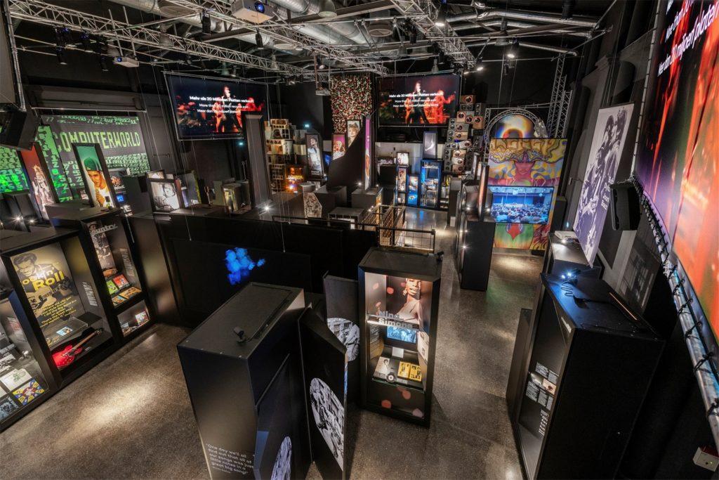 Die Audio-Guides erkennen, an welcher Stelle der Ausstellung sich die Besucher befinden, und spielen die entsprechende Musik. Auch weiterführende Informationen oder Interviews mit den Künstlern sind auf dem Audio-Guide abrufbar.