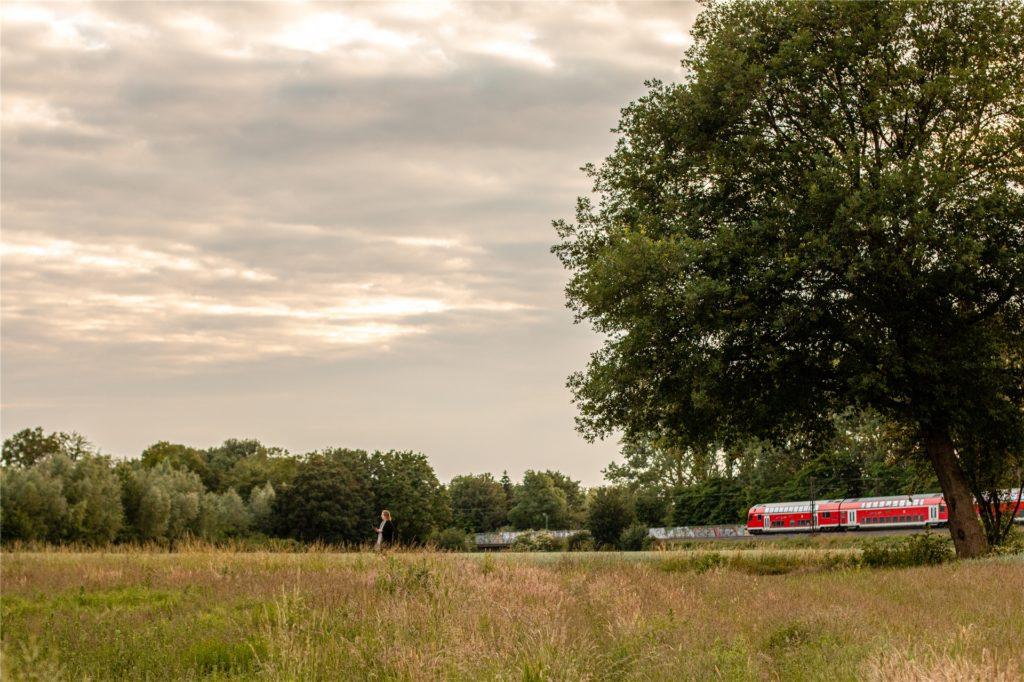 Während des Spaziergangs werden alltägliche Dinge bewusster wahrgenommen. Hier ist es ein Zug, der die ruhige Landschaft durchquert.