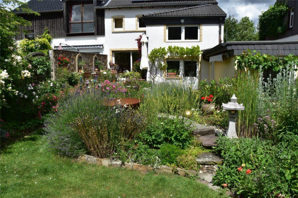 Der Blick vom Garten auf das Haus. Zwischen den Blumen steht eine Feuerstelle.