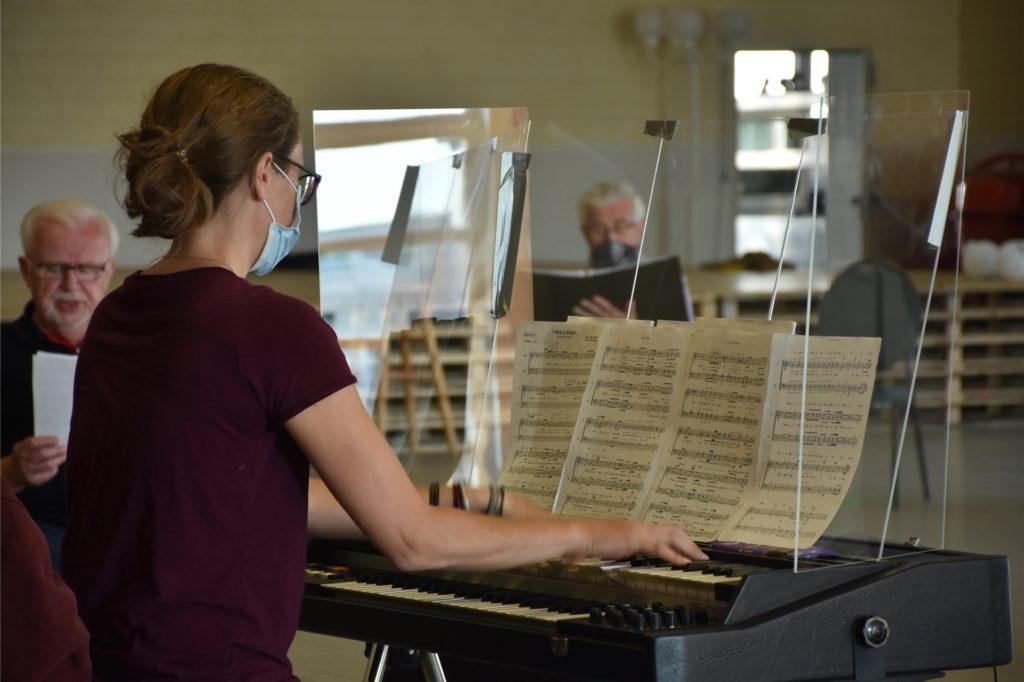Chorleiterin Eva-Maria Gröner hat sich für die Probe unter Corona-Bedingungen hinter Plexiglas verbarrikadiert. Genau wie die Sänger ist sie glücklich, endlich wieder proben zu können.