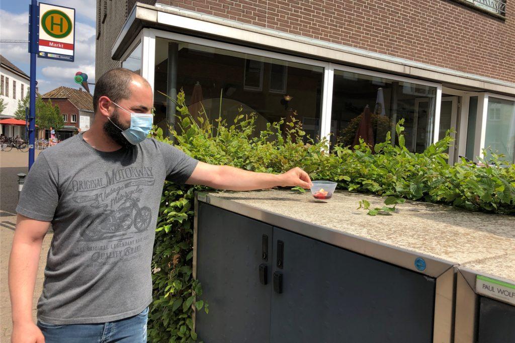 Maurizio Di Dino, Mitarbeiter des Eiscafés De Bona, platziert einen Becher mit Früchten und Amarenasoße abseits der Tische. Extra für Wespen.