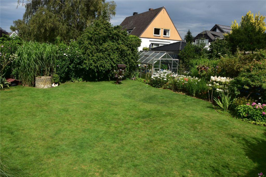 Ganz rechts das Gewächshaus von Holger Jannusch. In der Mitte des Gartens steht der Brunnen. Daneben ist die Hütte für den Rasenmähroboter.