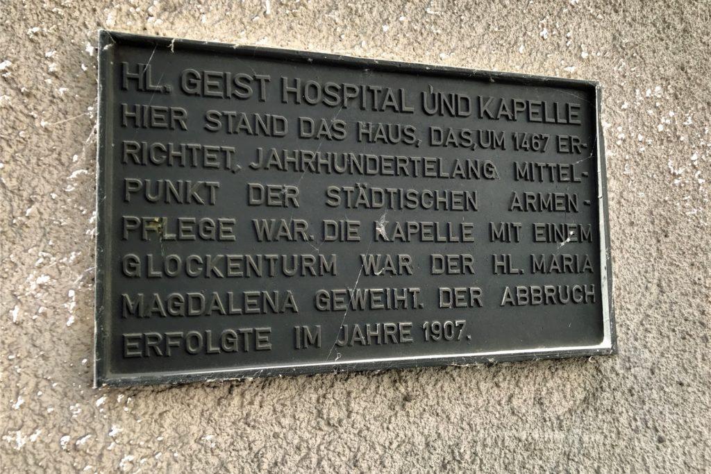 Eine Tafel am ehemaligen Standort erinnert heute an das Hospital und die Kapelle.