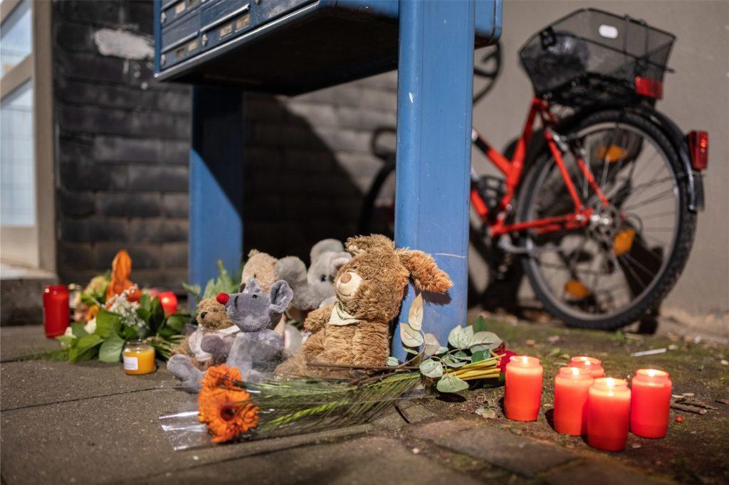 Teddybären, Kerzen und Blumen liegen und stehen vor einem Haus. Eine 27-jährige Mutter soll in Solingen fünf Kinder umgebracht haben.