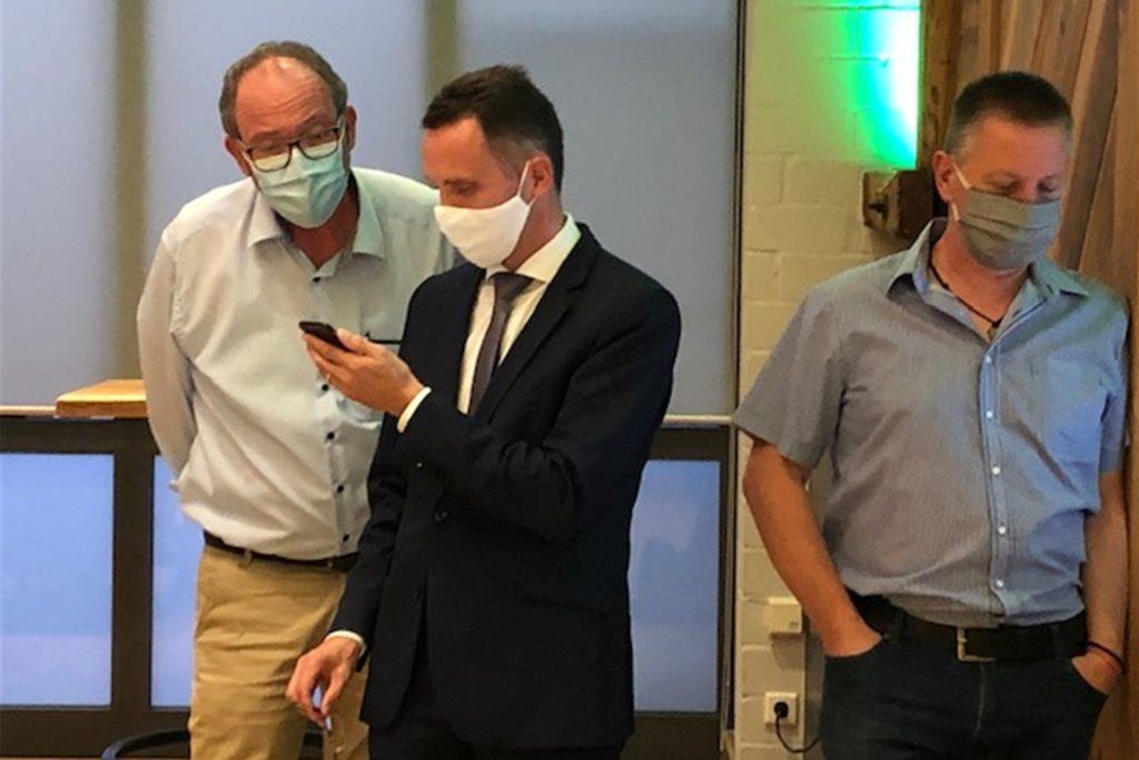 Der amtierende Bürgermeister, Dr. Bert Risthaus (M.), verfolgt die Zwischenergebnisse auf seinem Smartphone.