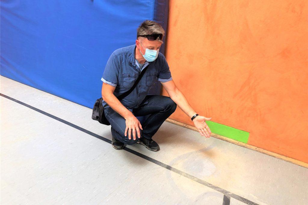 Dragan Barić zeigt auf den Dreck, der nach Abschluss der Ausbesserungsarbeiten in der Halle hinterlassen wurde.