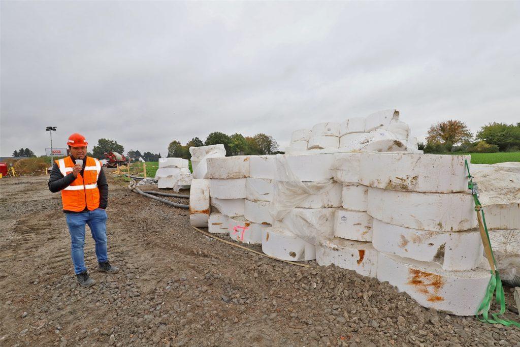 Projektleiter Fabian Holzmann zeigt die Styroporschablonen, mit denen zuvor die 310 Bohrlöcher aufs Baufeld gezeichnet wurden.