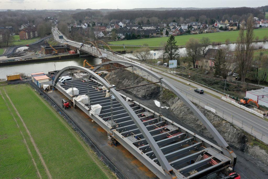 Hinten ist die alte Kanalbrücke zu erkennen, vorne wird an Land die neue Brücke zusammengebaut.