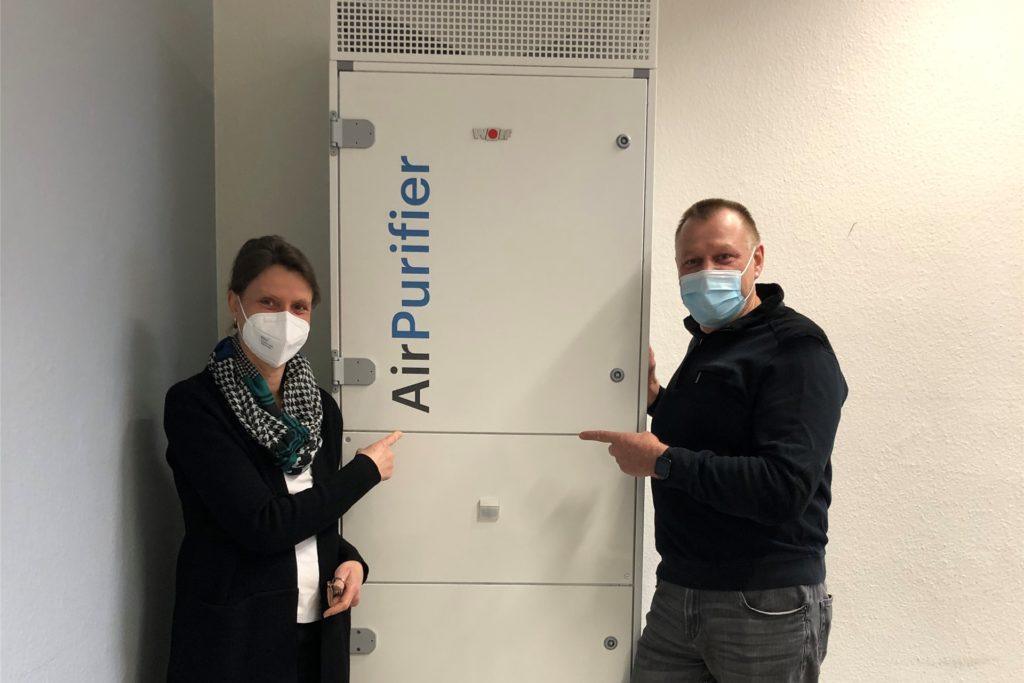 LBK-Schulleiterin Rita Vonnahme (l.) und Hausmeister Waldemar Strehl zeigen auf den 2,30m hohen und knapp 200kg schweren Luftreinigungsfilter. Das Lippe Berufskolleg ist mit insgesamt neun Filtern ausgestattet worden.