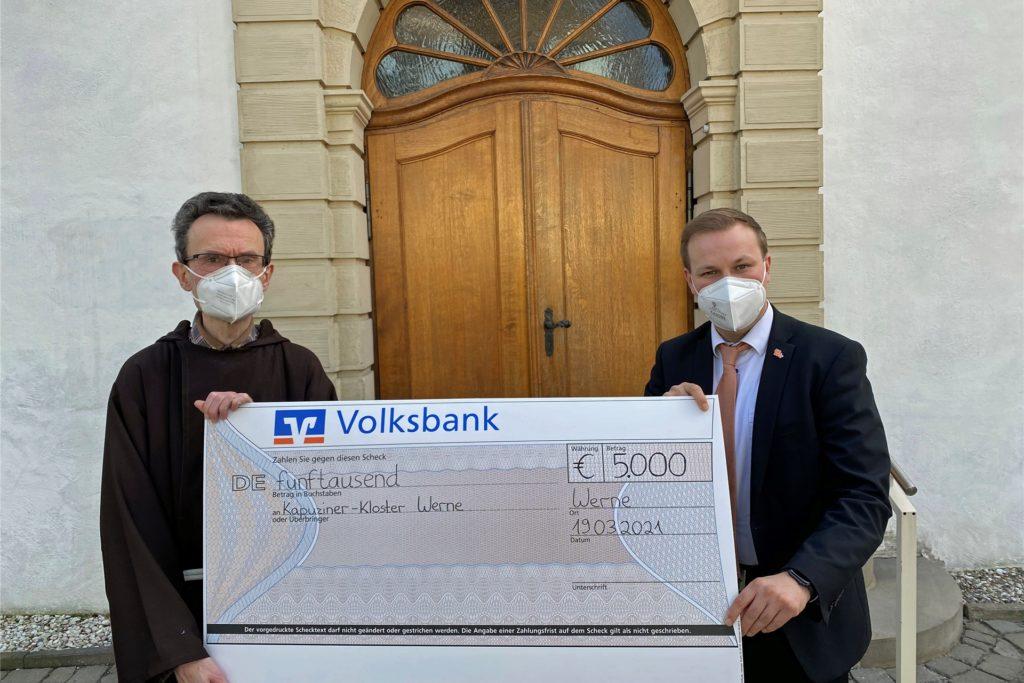 Der erste Scheck ist schon da. Philipp Gärtner (r.) überreicht im Namen der Volksbank einen Scheck über 5000 Euro an den Vorsteher des Werner Kapuziner-Klosters, Pater Romuald.