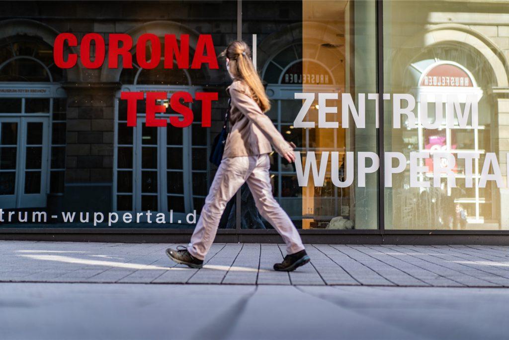 Eine Frau geht am Corona-Test-Zentrum in der Wuppertaler Innenstadt vorbei.