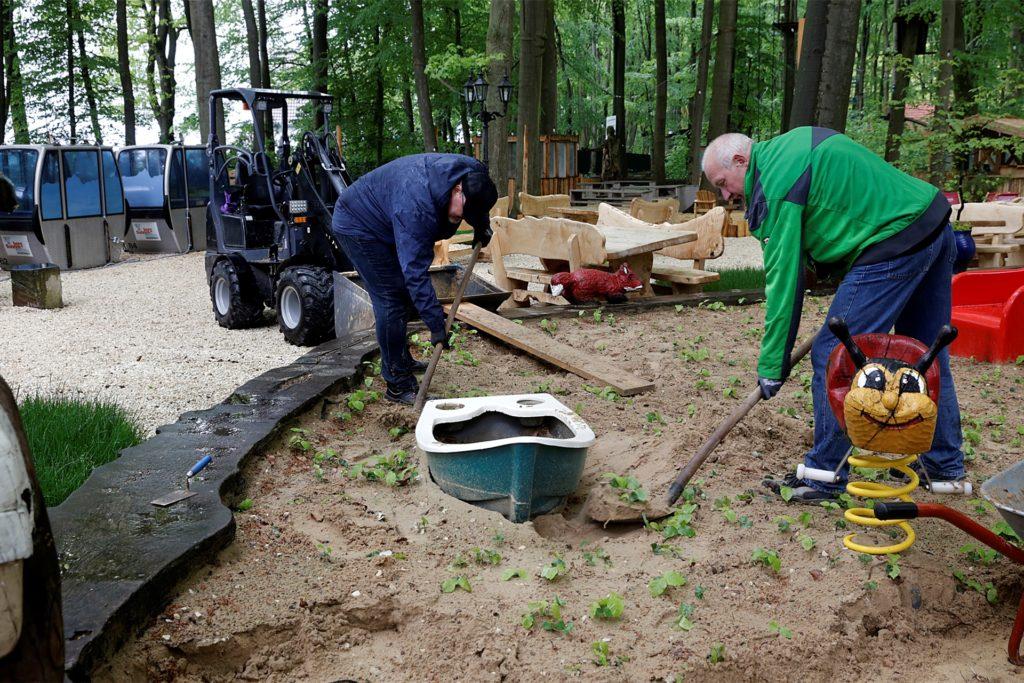 Im  Sand am Spielplatz wachsen kleine Buchen: Rainer Grawe (r.) und  Thorsten Schumann tauschen in Jupps Biergarten deshalb den Sand aus.