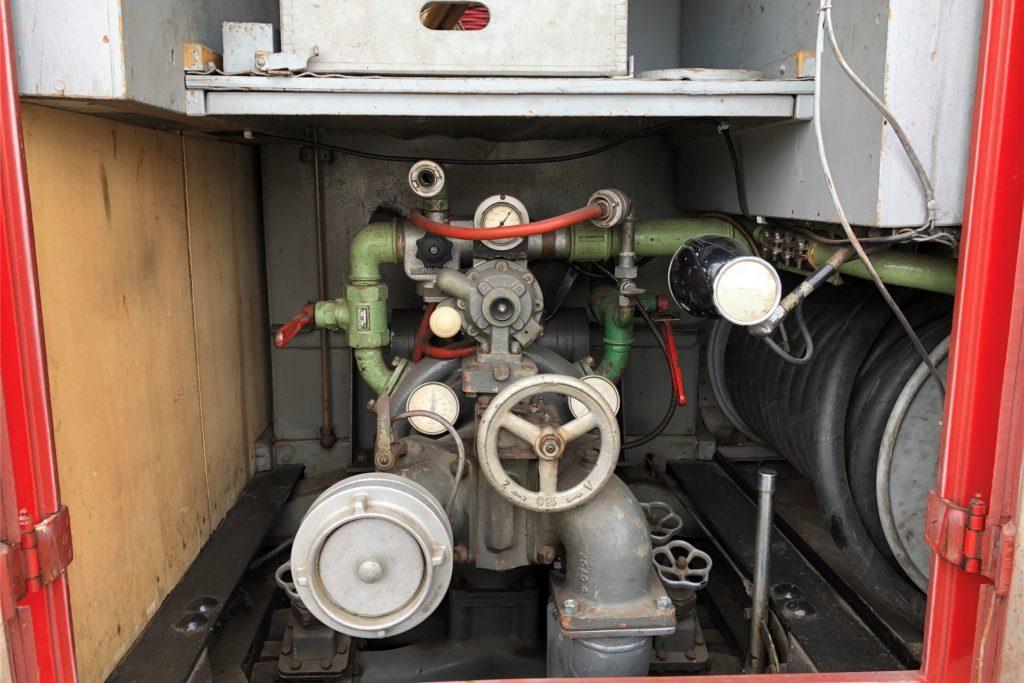 Das Herzstück eines jeden Tanklöschfahrzeugs ist ganz hinten: die Pumpe. Der Wasserstand wird in einem kleinen Rohr links neben der Pumpe angezeigt: Liegt die orange Kugel da ganz unten, ist kein Wasser an Bord.
