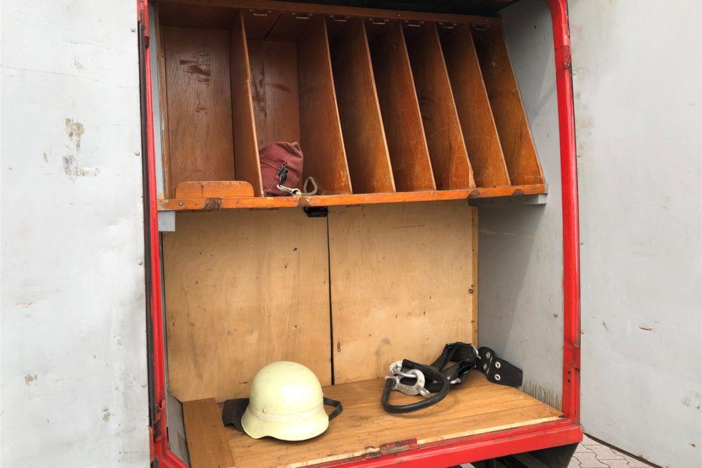 Helm und Feuerwehrhaltegurt liegen bereit.