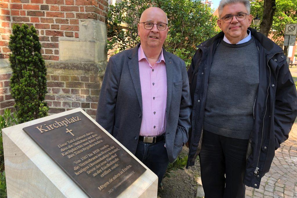Heimatvereinsvorsitzender Ernst Bennemann und Pastor Stefan Scho an der Sandsteinstele mit Bronzetafel. Auf der Tafel steht Wissenswertes über die Geschichte des Kirchplatzes.