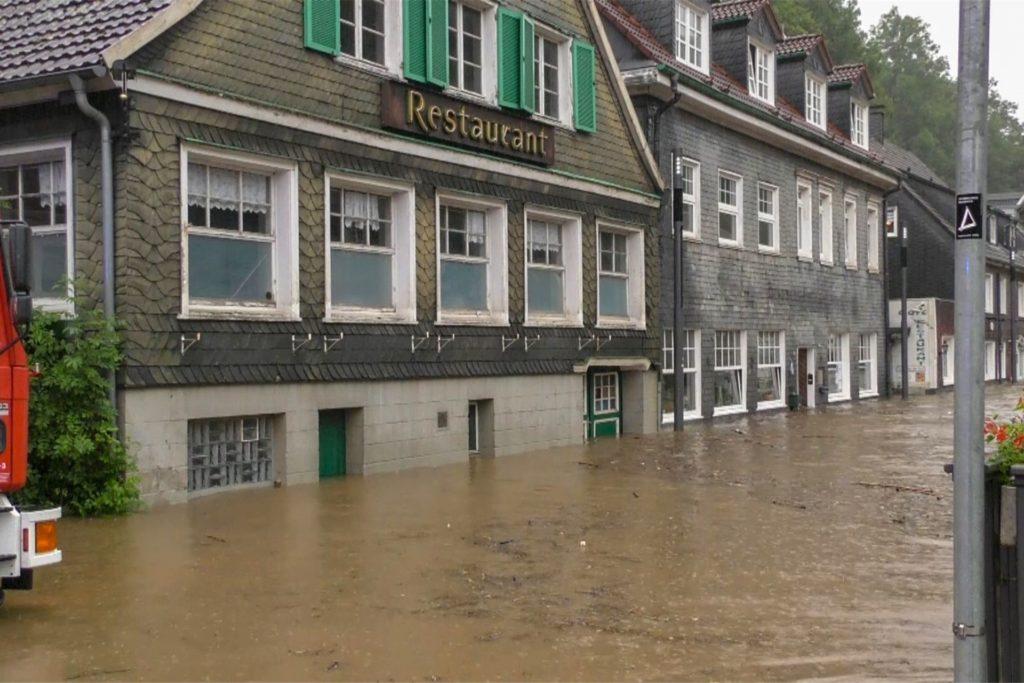 Eine Straße vor einem Restaurant in Solingen ist überflutet.