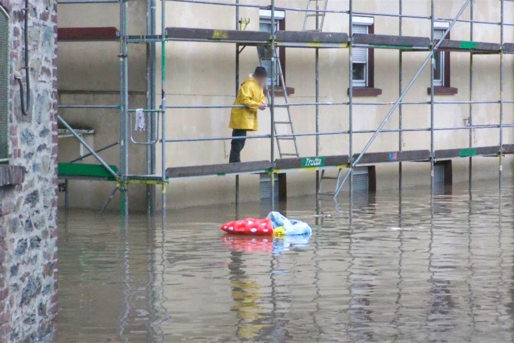 Ein Mann steht auf einem Gerüst und betrachtet die überflutete Straße vor dem Haus in Solingen.