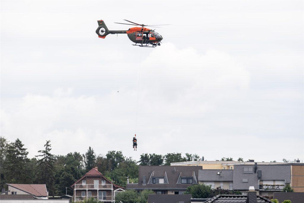 Mit Hilfe einer Seilwinde werden Menschen per Hubschrauber aus dem Ortsteil Heimerzheim gerettet.