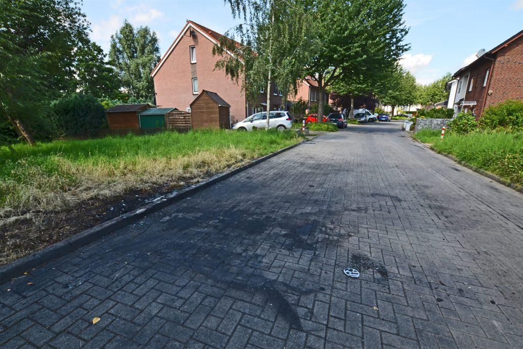 Ruß, Scherben und eine Markenplakette vom Kühler: Die Spuren des Brandes sind in den Deusener Wiesen noch sichtbar.