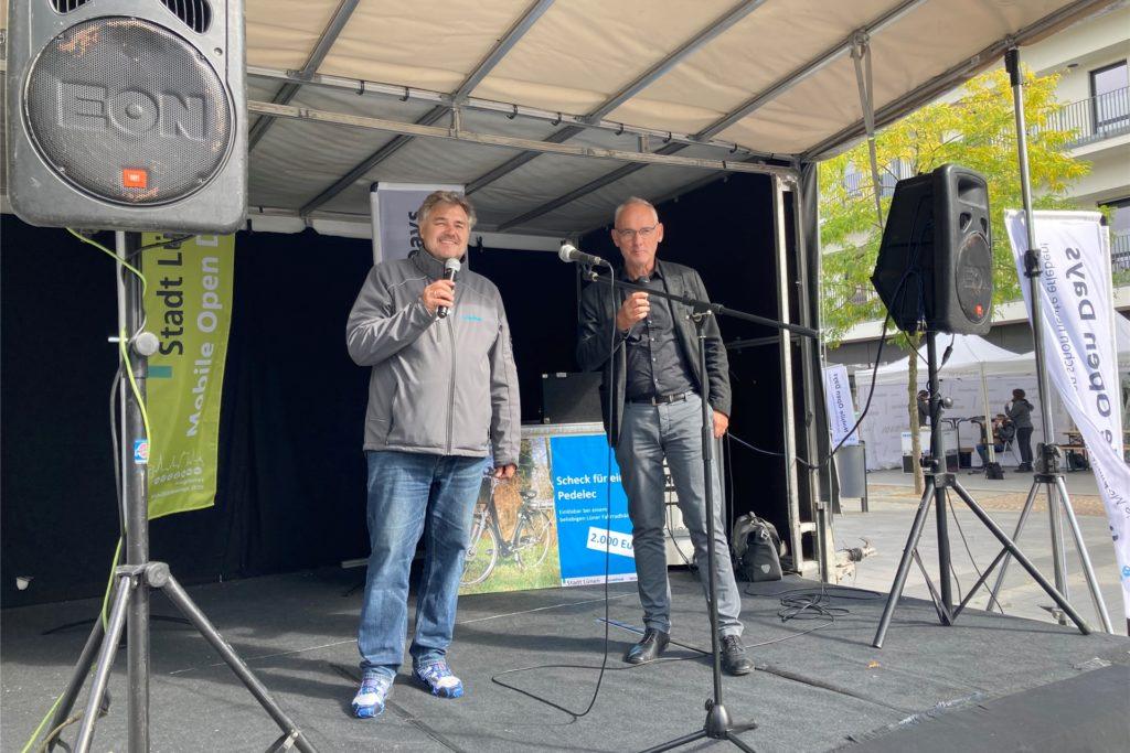 Dr. Christian Muschwitz, Geschäftsführer von raumkom (l.) und Arnold Reeker, Technischer Beigeordneter der Stadt Lünen, übergeben die Urkunden an die Stadtradler auf der Bühne.