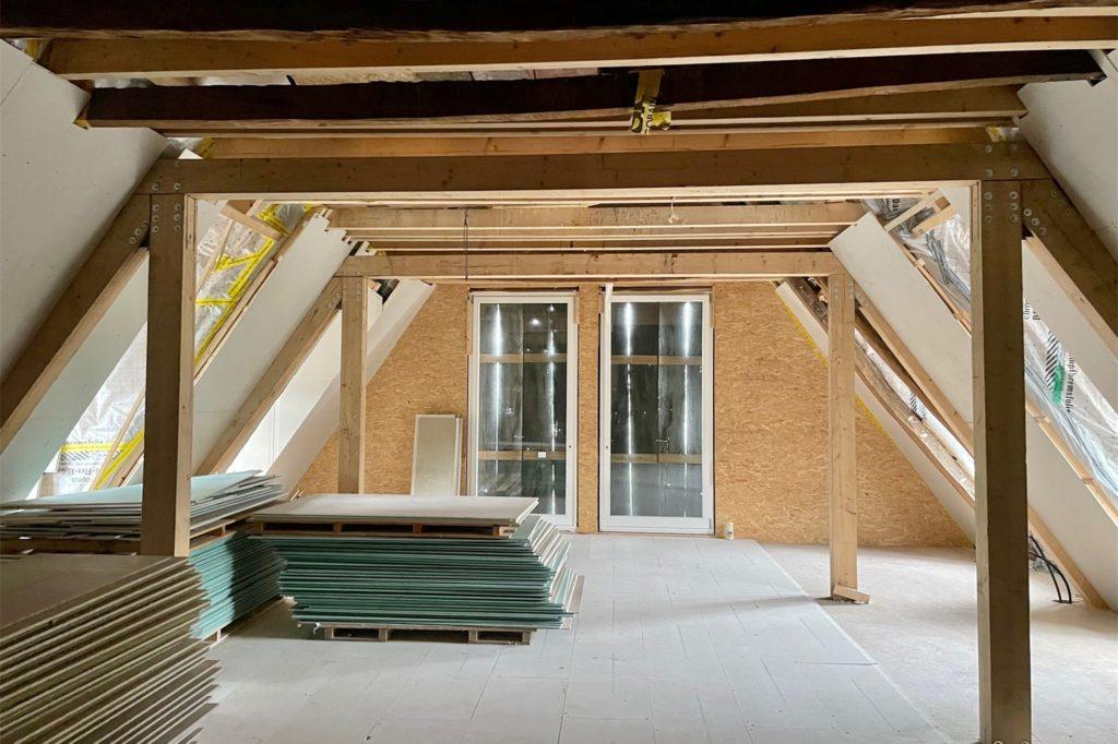 Im Dachboden ist die Küche und ein großer Saal. Die alten Fensterläden sind wie ein Vorhang zusammengefügt worden. Werden sie geöffnet, ist der Blick frei auf den Rodenbergteich.