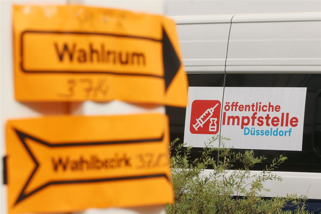 Vor einem Wahllokal in einer Schule und neben einer mobilen Impfstation für Covid-19-Impfungen weisen zwei gelbe Zettel den Wählern den Weg.